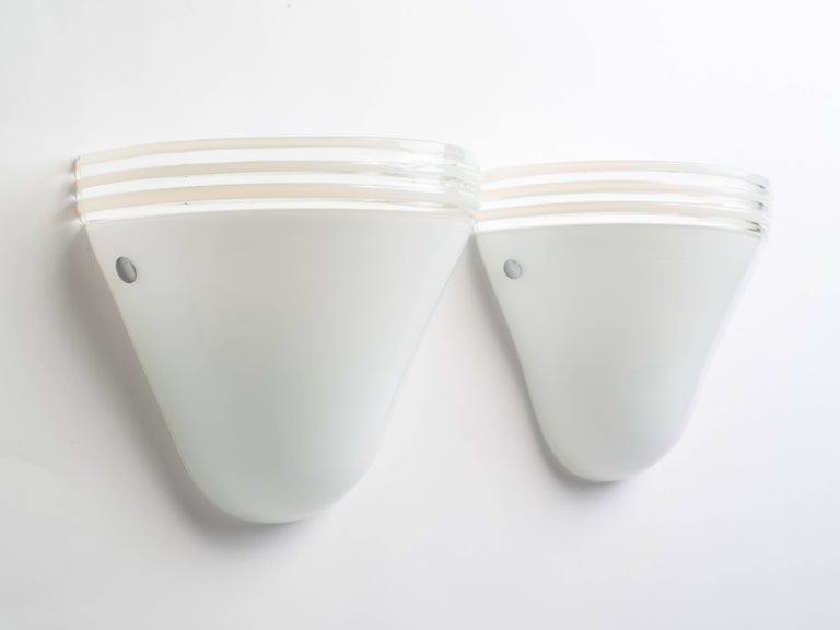 Pair of Mid-Century Modern sconces designed by Roberto Pamio and Renato Toso for Leucos. White Murano glass with clear glass bands along the tops. Feature polished chrome bolts and fitted with two lights each. Total of three sconces available.