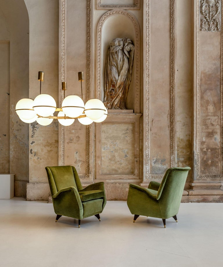 Iconic pair of green velvet armchairs by Isa. Tapered wood and brass feet and very elegant shape and comfortable seats. Original velvet upholstering.