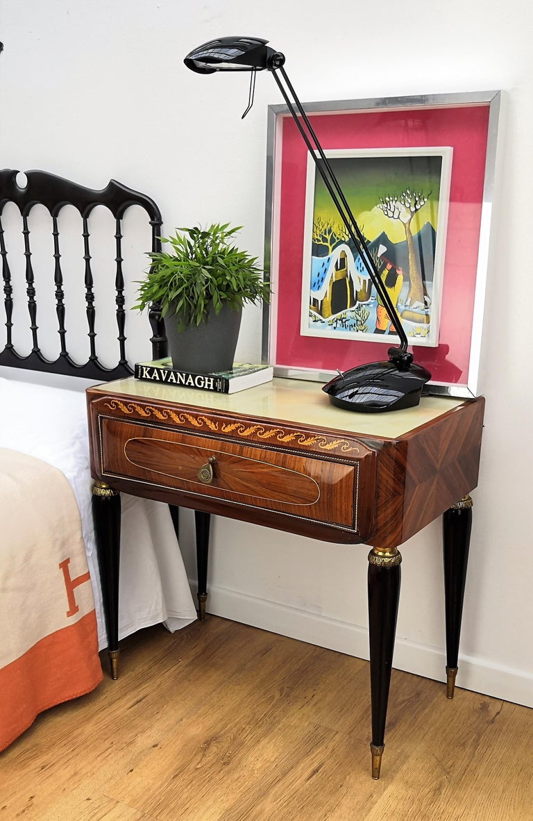 Very elegant and refined Italian 1950s neoclassical pair of bedside tables with inlay walnut veneer wood, drawer with brass handle, black legs with brass final and lacquered glass top. Those nightstands make a great look in any style bedroom, as a