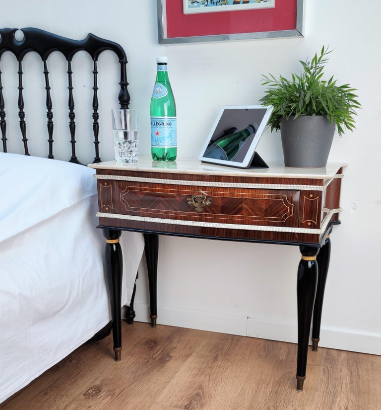 Very elegant and refined Italian 1950s neoclassical pair of bedside tables with inlay walnut veneer wood, drawer with brass handle, black legs with brass final and white marble top. Those nightstands make a great look in any style bedroom, as a