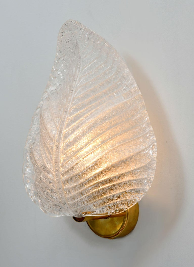Thick frosted Murano glass sculpted and textured into a leaf. Sits on a circular brass wall fitting. Gold flecks ensure a warm glow.
