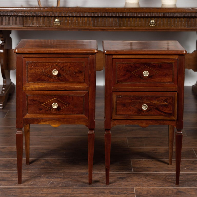 A pair of Italian neoclassical style walnut commodes from the mid-19th century, with tapered legs and inlaid diamond motifs. Born in Italy during the second quarter of the 19th century, each of this pair of walnut commodes features a rectangular top