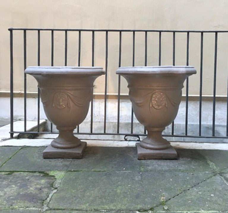 Pair of Italian neoclassical style stone paste gardens urns hand painted in mud color  Italian contemporary production in antique neoclassical style made in stone paste, which is stone sable add to the cement. Similar presence in the wonderful