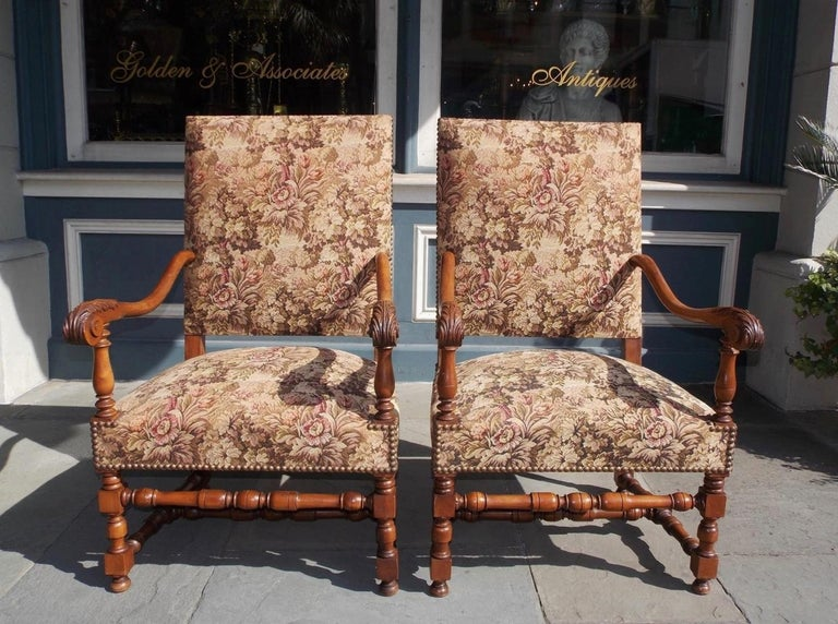 Pair of Italian neoclassical walnut arm chairs with upholstered squared backs, flanking scrolled acanthus arms, upholstered seats with brass tacks, and terminating on turned bulbous ringed blocked legs with the original connecting stretchers,