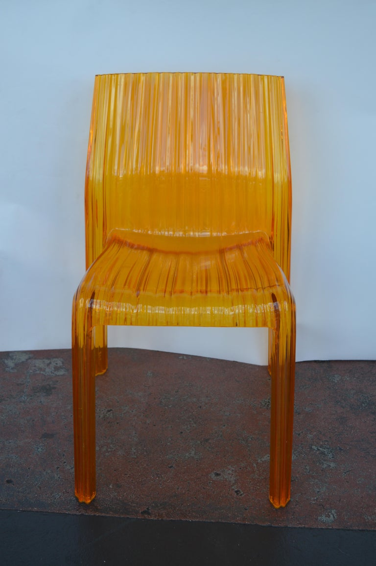 Two orange Lucite chairs by Kartell with the original stamp.