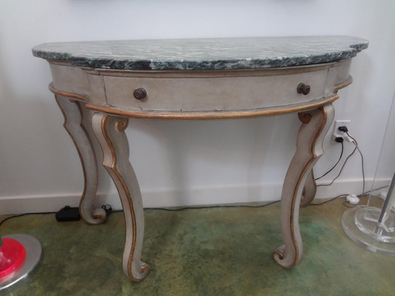 Stunning pair of Italian neoclassical style painted and giltwood console tables. This matching good sized pair of Italian painted and parcel gilt consoles feature beautiful legs, marble-tops and a single drawer. These versatile freestanding