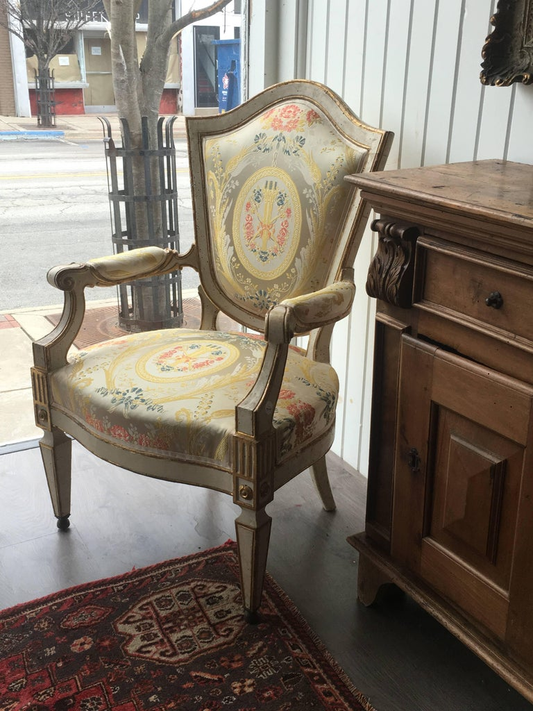 A pair of Italian painted fauteuils Florence, 18th century each having a Tassinari & Chatel silk-upholstered shield form padded back, padded arms with scroll hand holds and a shaped stuffover seat, raised on square tapering legs. Measure: Height