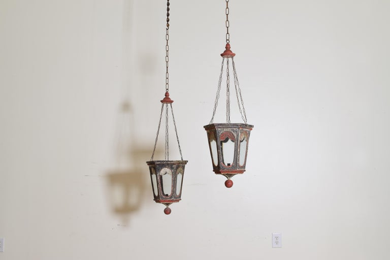 Hanging from turned wooden tops with 6 original small chains, the bodies of tapering form, each with a glass window, the single bobeche inside for a candle, decorated with painted swags, balls terminals.