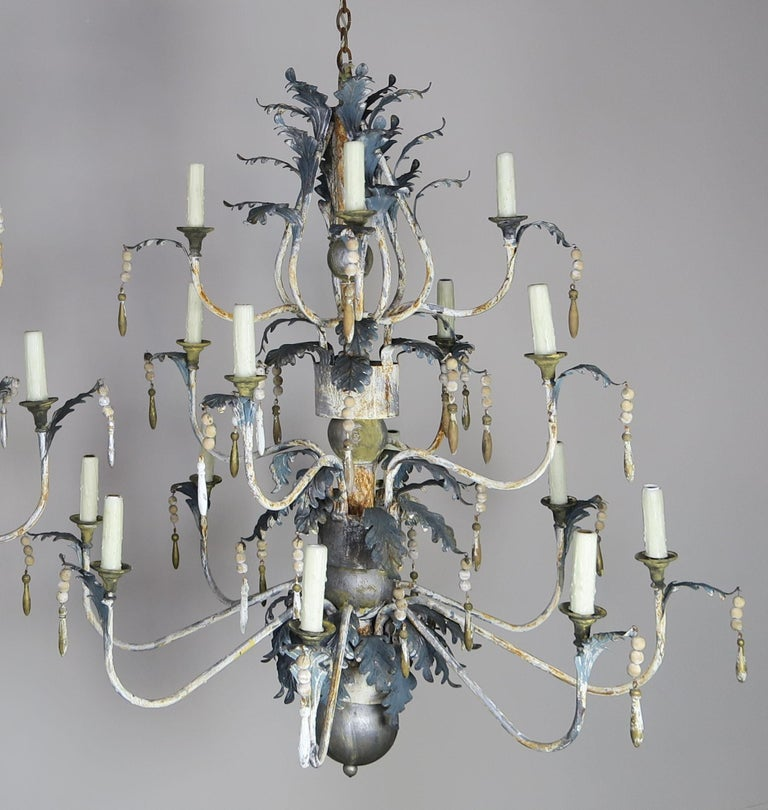 Pair of Italian painted wood and metal chandeliers with acanthus leaves and wood tassels throughout. Newly rewired and in working condition with chain and canopy included.