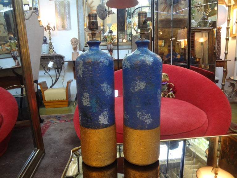 Stunning and unusual pair of Italian pottery lamps by Aldo Londi for Bitossi. These masterfully created glazed pottery lamps are in beautiful matte tones of blues and gold and would work well in a Mid-Century Modern or traditional interior. They