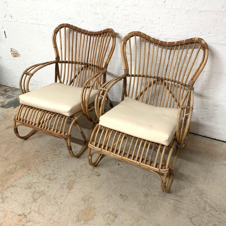 Unique pair of Italian chairs rendered in rattan and wicker with beige off-white cushions, by Bonacina, in the style of Franco Albini  Rattan, wicker, bamboo.