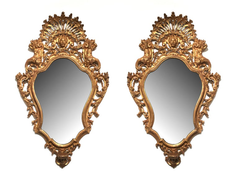 Italian Rococo (Florentine 19th century) pair of carved giltwood wall mirrors with a pierced fan shaped relief flanked by figures and a central head and all-over elaborately carved.