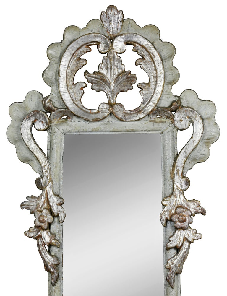 Each with an arched top with joined acanthus C-scrolls with central leaf over a mirror plate flanked by carved scroll and trailing leaf, the base with scrolled decoration and three candle arms. Provenance: Henry Forbes Bigelow. These sconces are