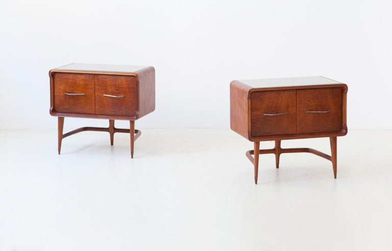 Set of two nightstands, manufactured in Italy during the 1950s  These two side tables has made of mahogany, brass feets, iron handles and retro-lacquered glass top  Completely restored, some joints of the legs have been re-glued, the original