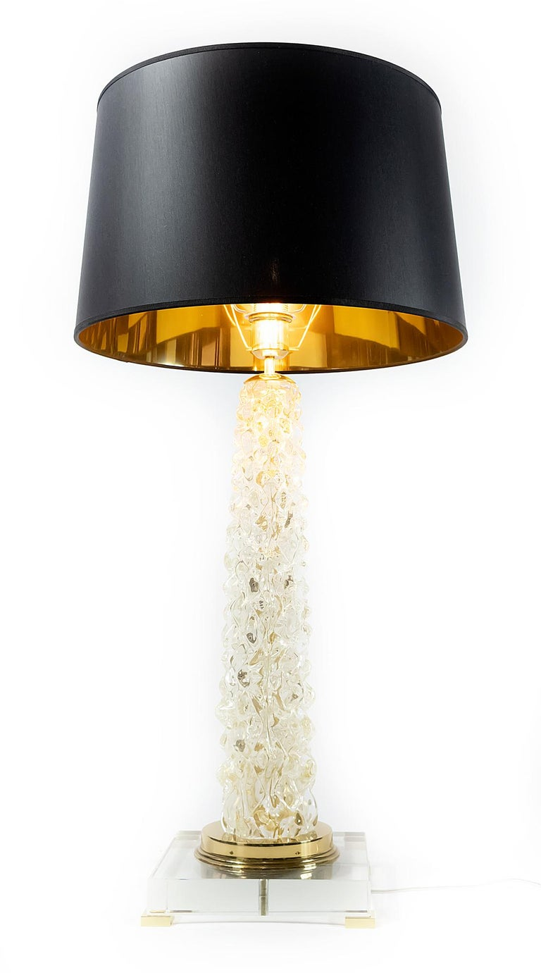 This pair of Italian table lamps are made of transparent Murano glass. The base is made of rectangular thick clear glass with small brass legs. Decorated with polished brass details. Both lamps are with new made satin finish black color textile