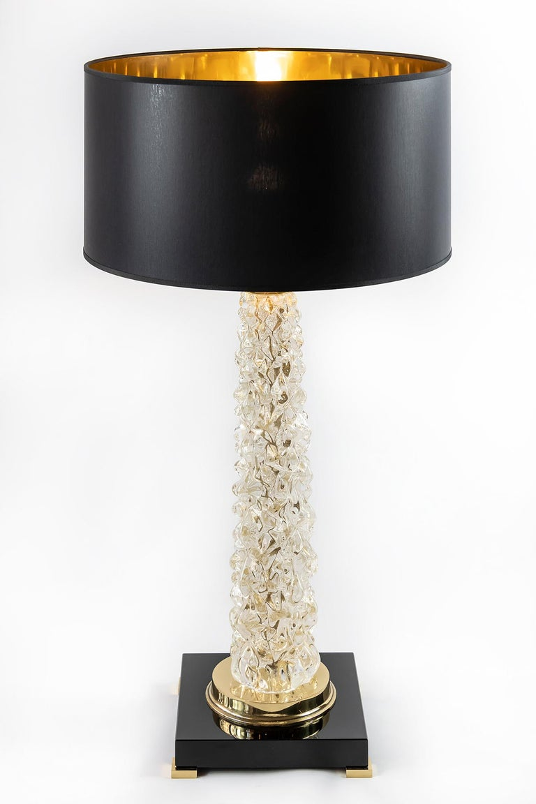 This pair of Italian table lamps are made of transparent Murano glass. The base is made of rectangular thick black glass with small brass legs. Decorated with polished brass details. Both lamps are with new made satin finish black color textile