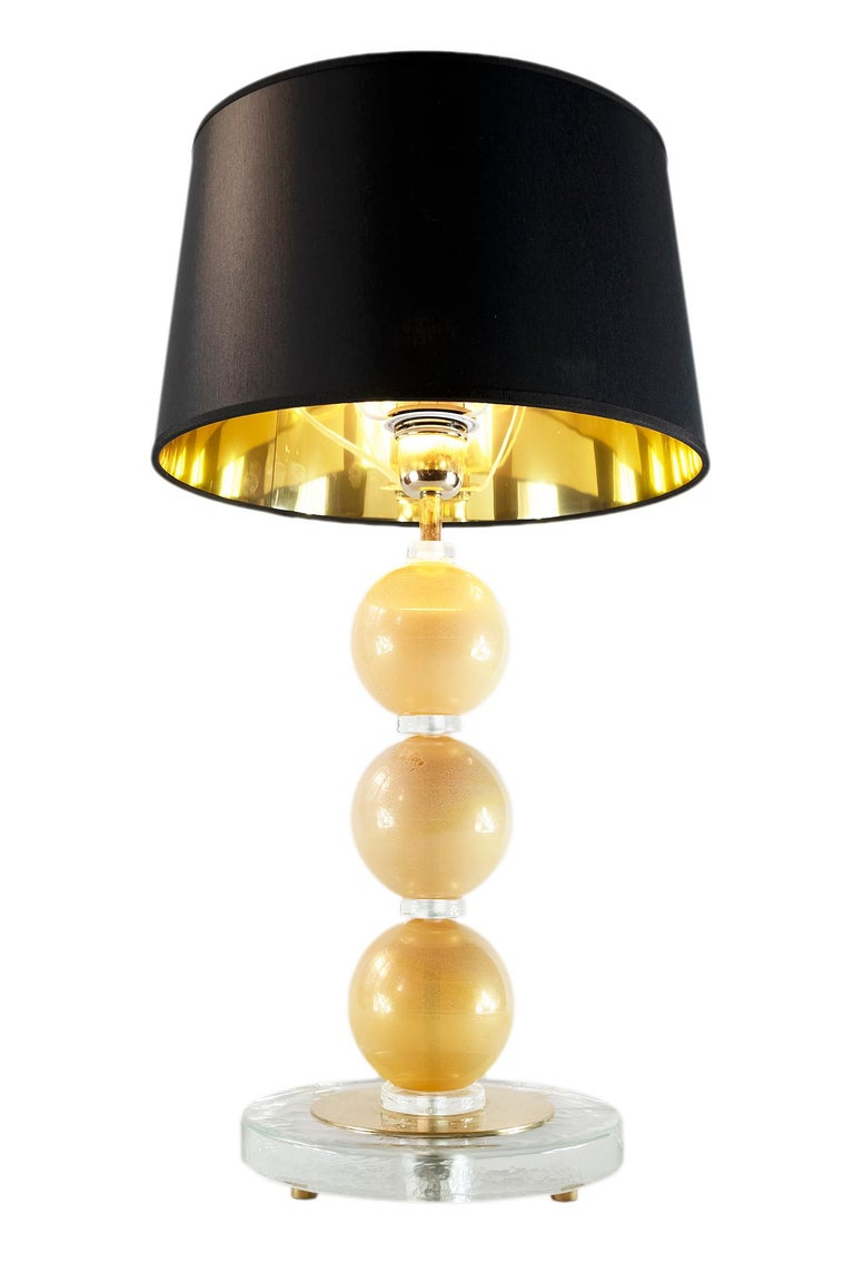 This pair of Italian table lamps are designed in Murano glass. The glass is lightly yellow with inlaid gold. The base is made of round form thick clear glass with small round brass legs. Both lamps are with new made satin finish black color