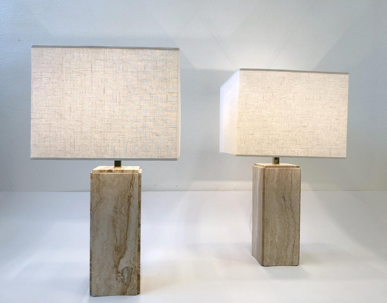"""A spectacular pair of Italian travertine and polish brass table lamps from the 1970s. The lamps have been newly rewired with all new brass hardware and new vanilla linen shade. The lamps are marked made in Italy. Overall dimension: 18"""" wide, 18"""""""
