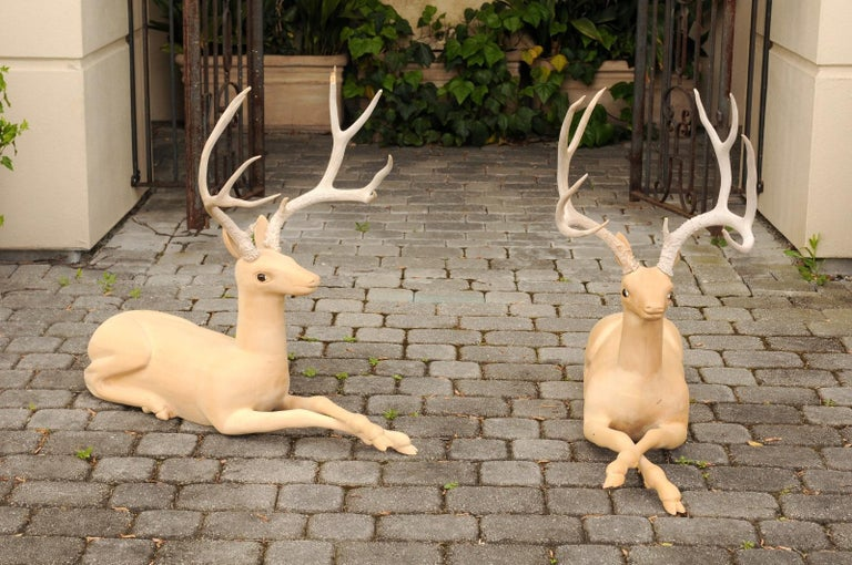 A pair of Italian wooden carved stag sculptures from the mid-20th century with large antlers. Born in Italy during the mid-century period, this charming pair of wooden sculptures depicts two stags carved in a minimalist style and topped with large