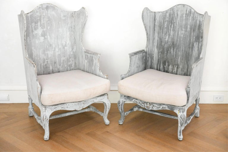Pair of Impressive, highly stylish and unique Italian painted wood frame wing back arm chairs that will bring presence to any room. Chairs have a full wood frame and a loose cushion. The painted wood frame. is intentionally distressed. The cushions