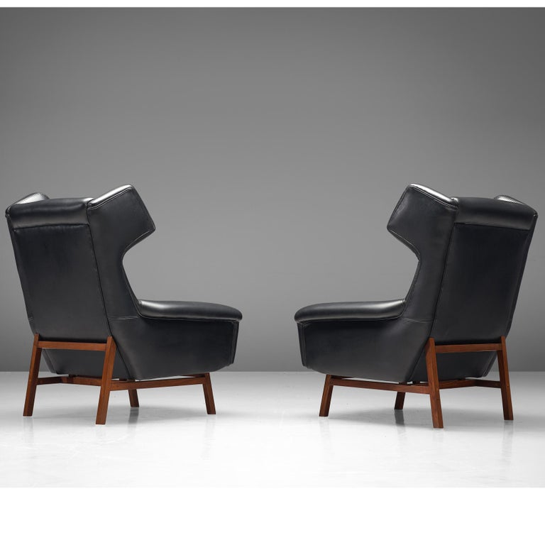 Pair of lounge chairs, leather, teak, Italy, 1960s  This wonderful pair of sturdy and voluminous lounge chairs show nice details and elegant lines. The 'ears' and armrest are beautifully formed. The backrest is tufted for a more Classic look and