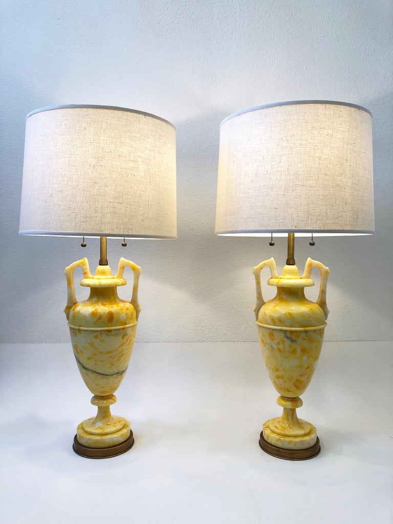 """Spectacular pair of Italian yellow marble and satin brass table lamps by Marbro Lamp Co.  Vibrant yellow color. Newly rewired and new vanilla linen shades.  Measurements: 38"""" High and 18"""" Diameter."""