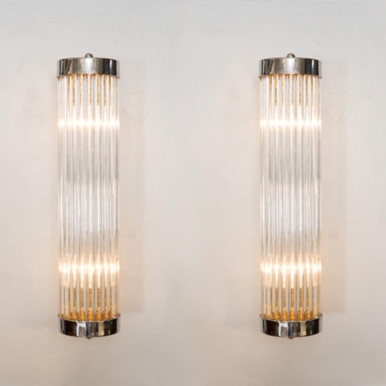 Contemporary Art Deco inspired Italian wall lights in the style of 'Venini'. Each light comprises of a circle of slim Murano glass rods capped top and bottom by round brass plates that attach with two slim brass arms to a brass wall bracket. Two