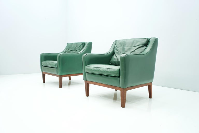 Pair of beautiful lounge chairs in green leather and wood frame (teak). The pillows are partly filled with down. The set was bought together with the matching 2-seat sofa in 1958. Origin Italy. Measures: H 76.5 cm, W 70 cm, D 71 cm, SH 40 cm. Good