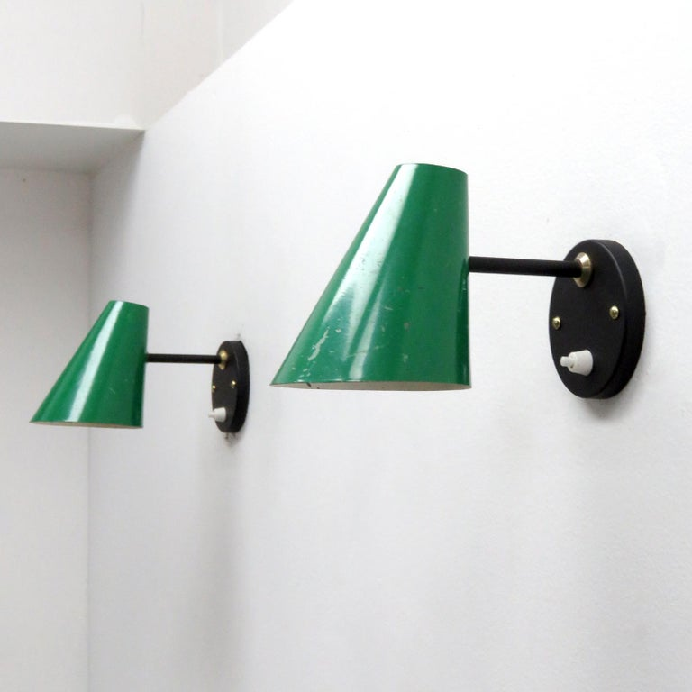 Elegant pair of articulate wall sconces by Jacques Biny, open top, green enameled metal cones on a ball joint arm with brass accents, individual on/off switch on each backplate.