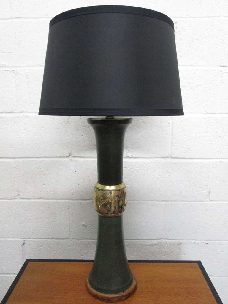 Pair of James Mont style lamps. The lamps have patinated green metal body with wood base and a brass decorative trim. Shades not included.   Measures: 30