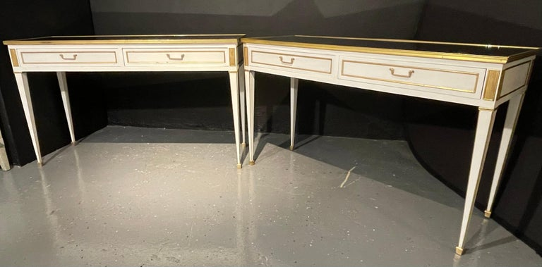 Pair of console or sofa tables each having a clean mirrored top set in a bronze frame supported by an apron sporting two drawers each bronze mounted with bronze drawer pulls and bronze cookie cutter corners. The pair having matching apron sides. The