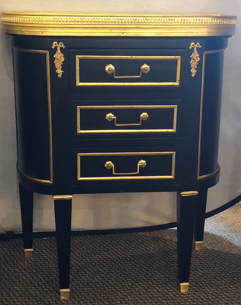 Pair of Jansen inspired marble-top galleried ebonized end tables and or nightstands with three drawers. These Hollywood Regency end tables will shine next to any bed or sofa and can surely sit on their own in most room settings. The rounded sides