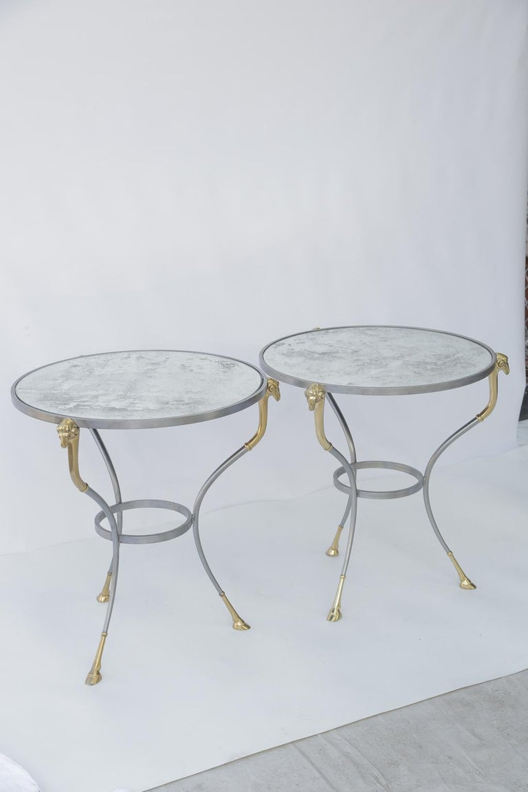 Pair of gueridon end tables, in the manner of Maison Jansen, each having a round top of antiqued mirror, on table bases of polished steel, raised on three curving legs, headed with ram's masks of brass, ending in cloven-hoofed feet, and joined by a