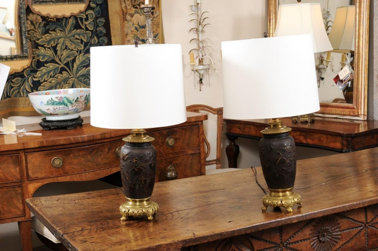 The pair of Japanese bronze lamps with foliage/bird decoration and brass mounts. The price is with out shades.