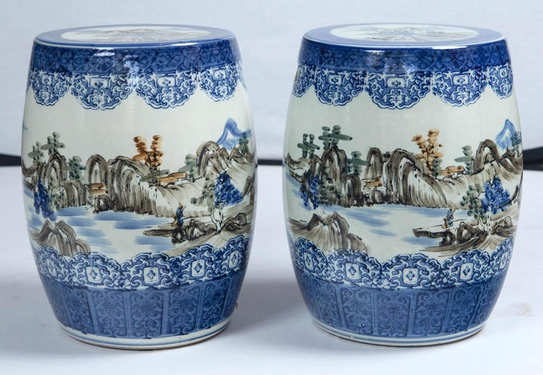 Pair of Japanese ceramic garden stools, early 20th century. Cobalt blue glaze design border at top and bottom. Overall rural landscape with mountains and lake. Design reminiscent of Japanese watercolor paintings.