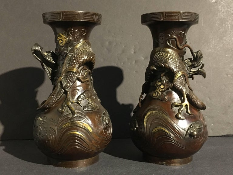 A pair of well cast and dramatic Japanese parcel gilt bronze dragon vases, Edo period, early 19th century. The heavy bronze vases of pear shape, each with a single writhing dragon cast in high relief dancing in the clouds. Under the dragons,