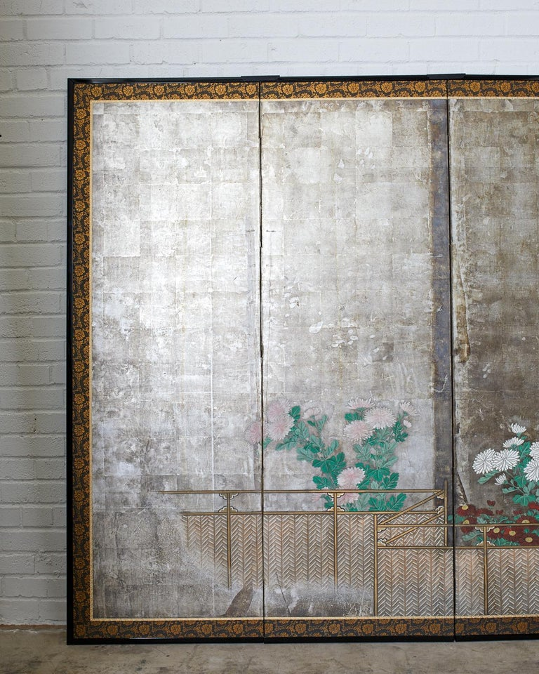 Remarkable pair of early 19th century Japanese late Edo period screens depicting summer chrysanthemums growing along a brushwood fence. Ink and color pigments over a dramatic silver leaf ground. Kano school influence with moriage flowers. The love