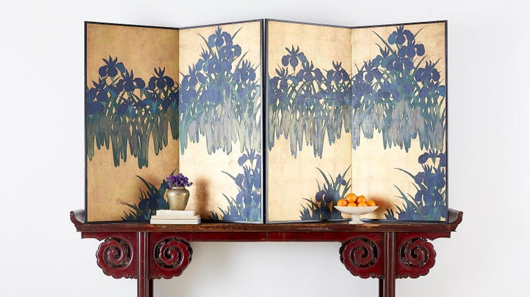 Dramatic pair of Japanese two-panel screens depicting Kakitsubata or flowering Irises on a gilt gold leaf background after Ogata Korin (Japanese 1658-1716). The screens feature abstracted blue Japanese irises in bloom with green foliage having a