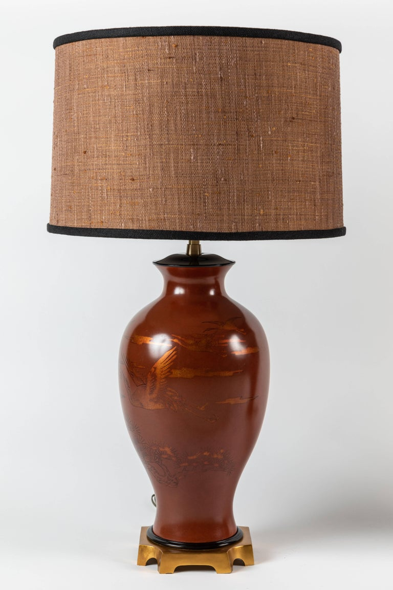An exquisite pair of red ochre urn-shaped table lamps depicting flying storks / cranes and Japanese scenery. The urns are situated on a gilded rectangular platform. The urns are a sturdy paper mâché material.  Offered with newly-designed custom
