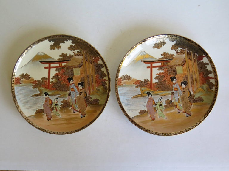 These are a good pair of Japanese earthenware plates with hand-painted and gilded Satsuma decoration which we date to the late Meiji period, circa 1900.  Each plate is circular, well hand decorated with a landscape scene depicting women wearing