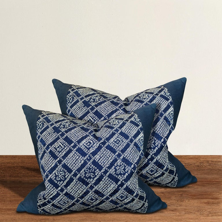 A pair of pillows made from vintage Japanese blue and white indigo shibori silk panels with an incredible geometric grid pattern with stylized flowers. Filled with down.