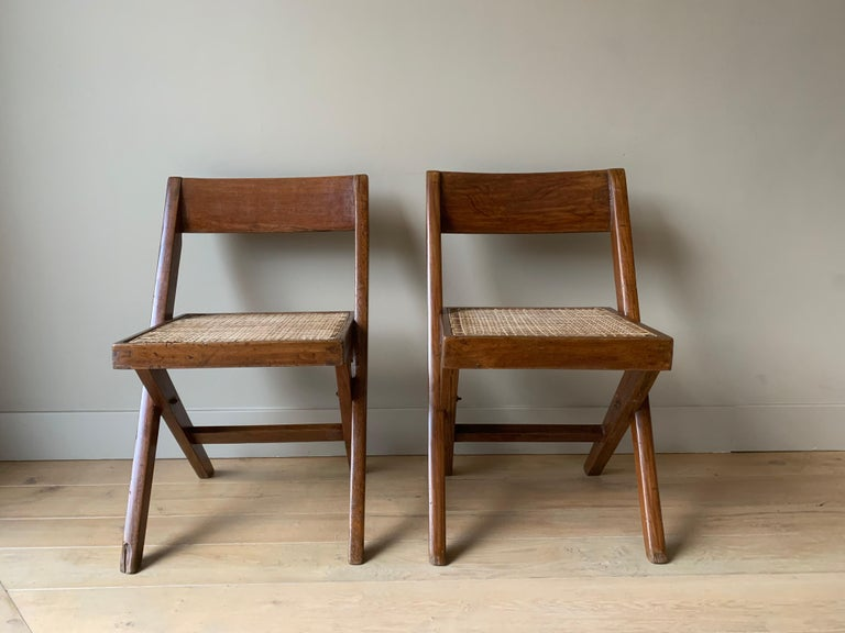 "A good authentic set of two Chandigarh chairs. Artisanally and locally made with pegged solid teak and braided canework in the 1960s. This type is known as the Library chair. The x- ""frame"" is beautifully complemented with the convex 'banner' type"