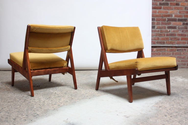 Early pair of Jens Risom for Jens Risom Design Inc. low lounge chairs model #U-431 (this chair first appeared in the 1955 Jens Risom Design Inc. catalog and was already out of production by 1959). Composed of armless, walnut frames boasting sharp