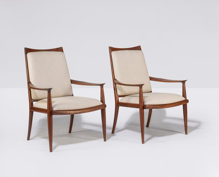 Pair of walnut armed lounge chairs by well-noted California craftsman John Nyquist.   Well made and finely detailed.   Newly upholstered.