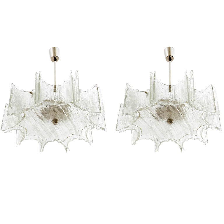 A pair of star shaped ceiling lights by Kalmar manufactured in Austria in midcentury, circa 1970 (late 1960s or early 1970s). They are made of frosted ice glass pieces mounted on a white lacquered frame and a nickel-plated brass stem and