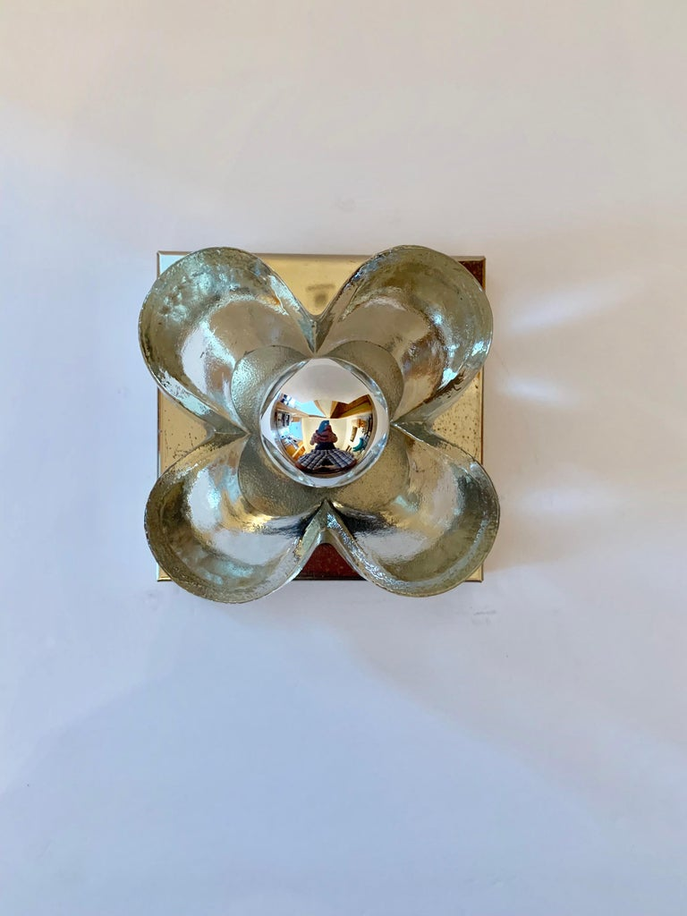 A pair of polished brass wall lights with thick glass floral shades. Newly rewired. Standard sockets.
