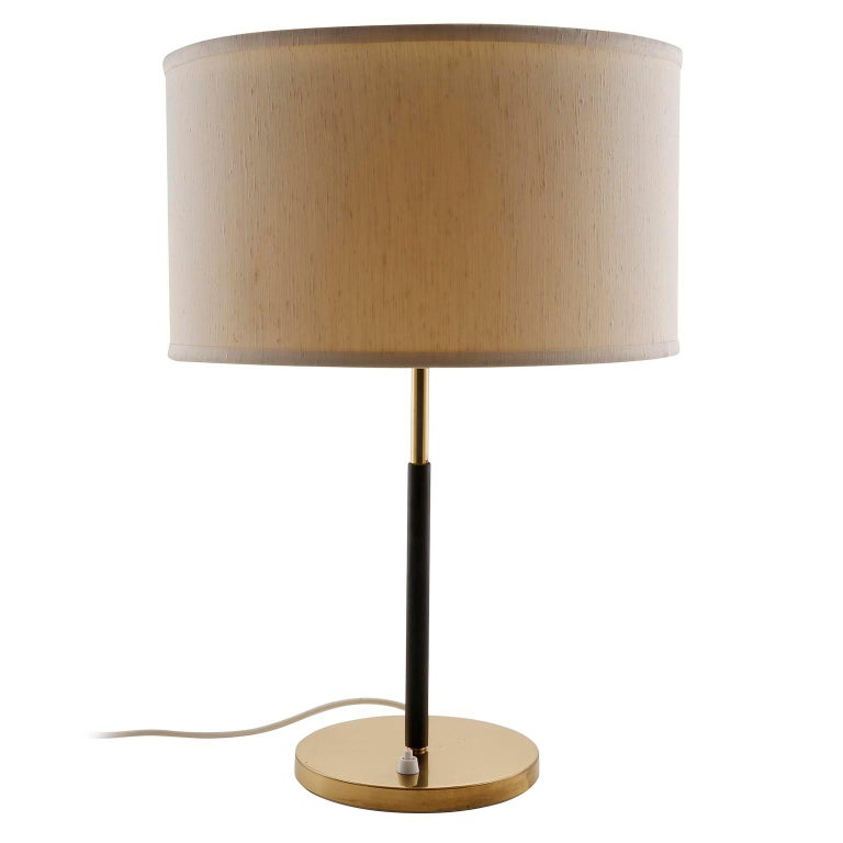 A pair of table lamps by J.T. Kalmar, manufactured in midcentury, circa 1960. They are made of a brass covered base, a covered stand with dark brown leather, brass fittings, and a cream colored lampshade. Each lamp takes two standard screw base