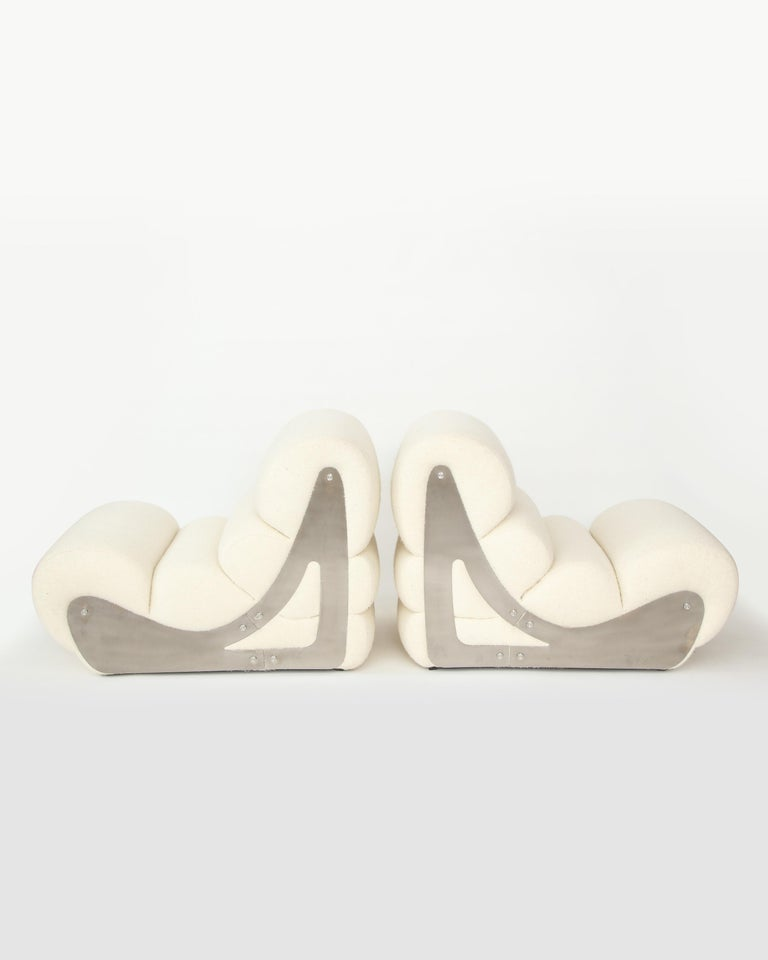Elegant armless lounge chairs comprised of metal and upholstery, produced by the French manufacturer Kappa, circa 1970s France. Fully restored and upholstered in a crème bouclé. Satin finished metal frames.   These forms are exceedingly ergonomic