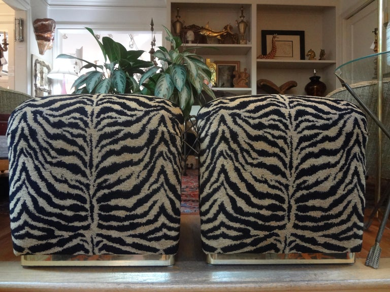 Stunning pair of Karl Springer style waterfall benches or ottomans with brass bases. These beautiful Hollywood Regency benches have been professionally upholstered in black and gold tiger print chenille. These midcentury stools are very comfortable!