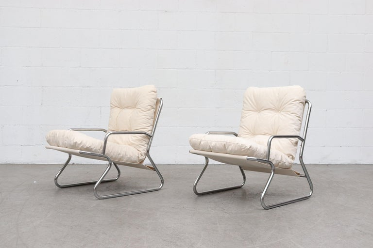 Pair of tubular chrome and natural canvas upholstered lounge chairs newly upholstered sling support and cushions, chrome frames in original condition with wear consistent with their age and usage. Set price. Another similar set is available and